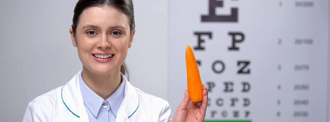 Zanahoria, la hortaliza que cuida tu vista: mujer oftalmólogan con una zanahoria en la mano