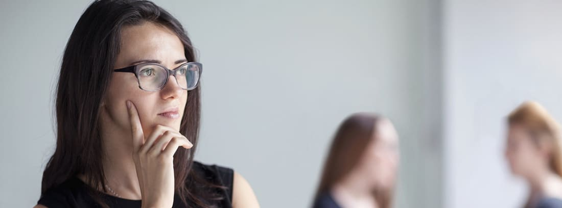 ¿Qué es el trastorno de personalidad evitativa?: chica joven con gafas y las manos en la barbilla dudando, al fondo dos mujeres hablando