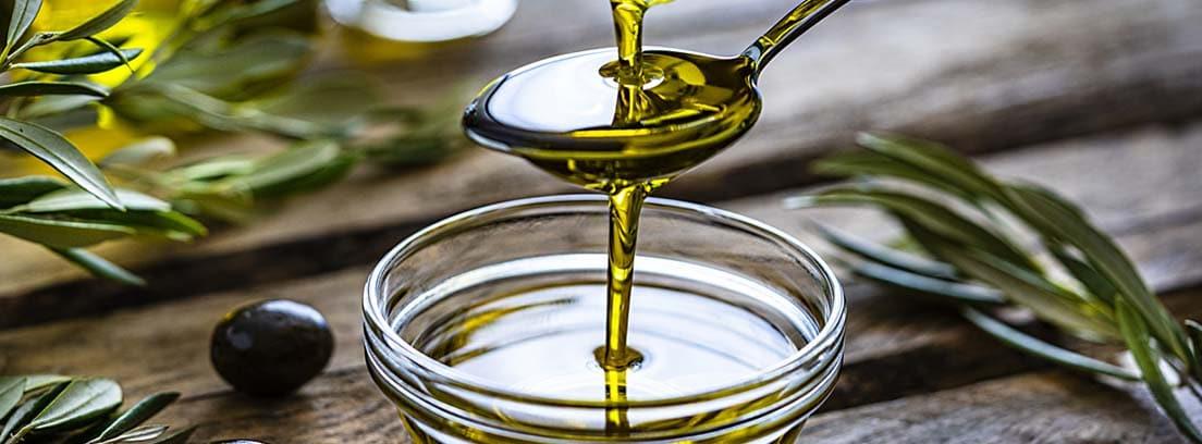 Los mejores aceites para cocinar y cuidar nuestra salud: aceite de oliva cayendo de una cuchara a un bol de cristal