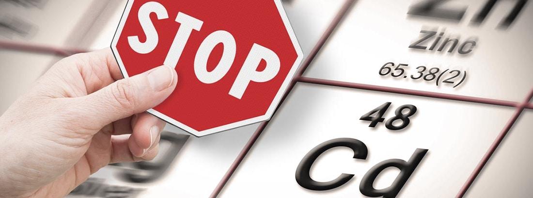 ¿Qué es el cadmio y qué alimentos lo tienen? simbolo del cadmio en la tabla periódica y unas manos sujetando una señal de stop