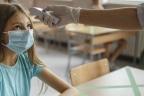 LOS NIÑOS ANTE LA VUELTA AL COLE Y LA NUEVA REALIDAD DEL COVID-19: niña en el colegio con mascarilla y profesor tomando la temperatura