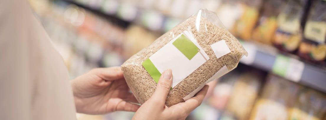 Consejos para comprar productos sanos: mujer con una bolsa de cereales mirando la etiqueta