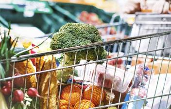 Consejos para hacer una compra saludable: mujer con un carrito de compra en supermercado lleno de verdura y frutas