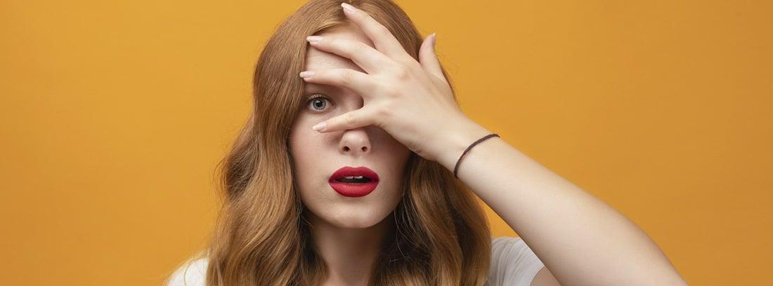 ¿Por qué sentimos vergüenza ajena?; mujer con la mano tapándose la cara y dejando abierto un ojo