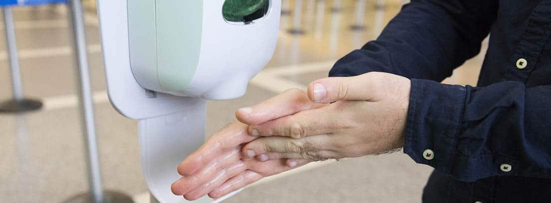 Ge3l hodroalcohólico: dispensador de gel hidroalcohólico y unas manos utilizándolo