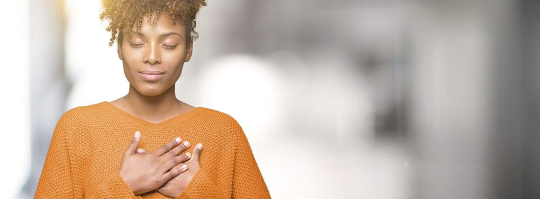 Personas altamente sensibles: chcia joven con sueter naranja, los ojos cerrados y la mano en el pecho