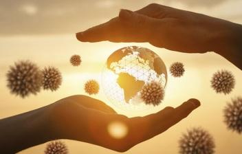 Covid-19 ¿pandamia o sindemia? Bola del mundo entre dos manos y virus alrededor