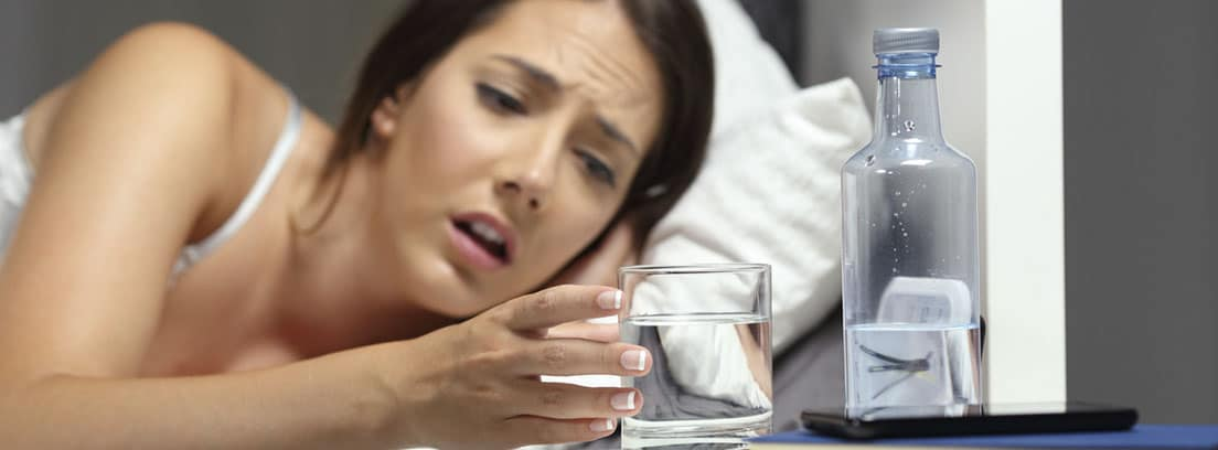 Beber agua: mujer en la cama cogiendo un vaso de agua
