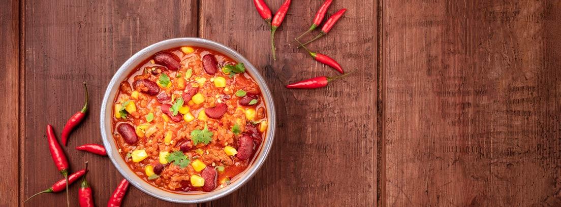 Picante, beneficios y contraindicaciones: plato de comida picante con chiles alrededor sobre una mesa de madera