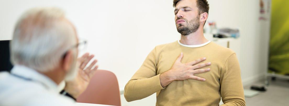Dolor torácico: chico joven en consulta de médico con la mano puesta en el tórax en señal de dolor