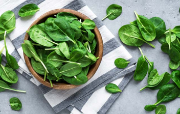 Beneficios de las espinacas: bol de espinacas sobre paño de cocina