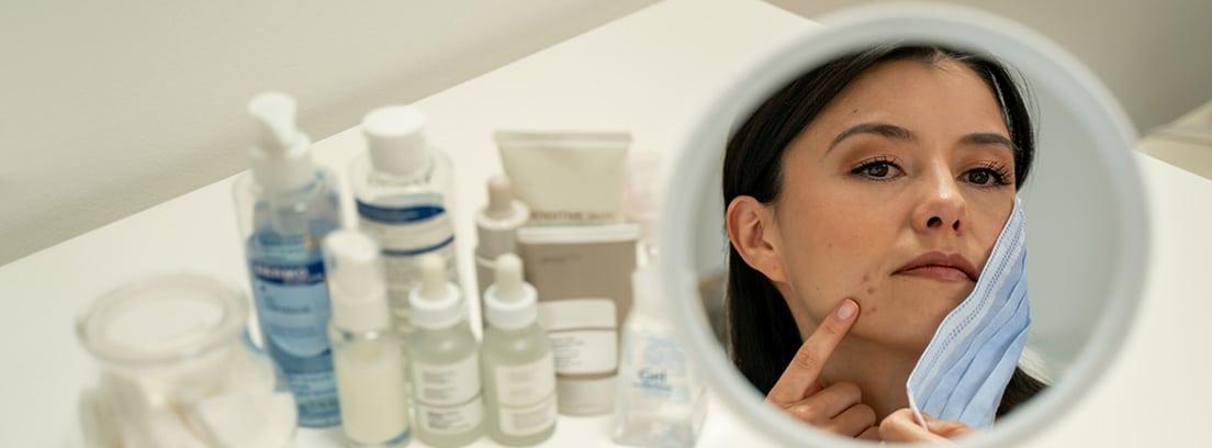 Problemas de piel causados por las mascarillas y geles anti-Covid: mujer ante un espejo con acné a consecuencia de la mascarilla