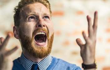 Trastorno explosivo intermitente: joven con las manos levantadas y la boca abierta