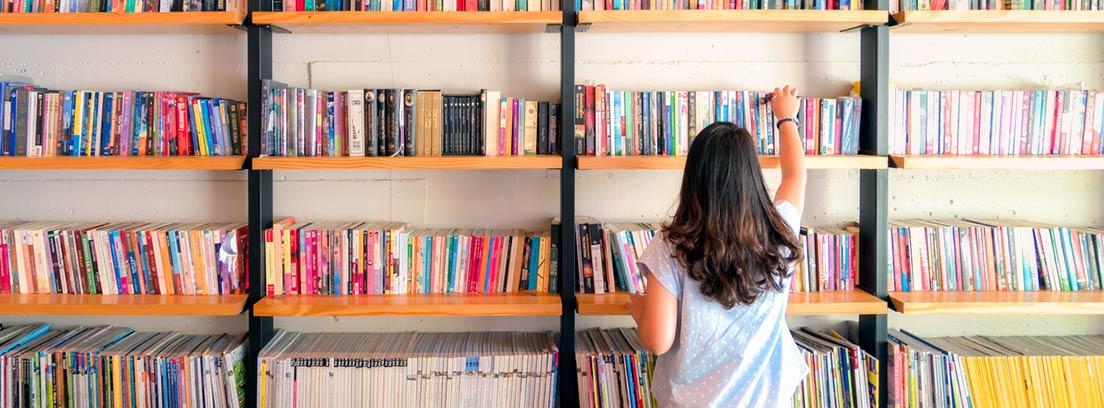 9 Beneficios de la lectura en la salud : chica de espaldas ante una estantería llena de libros
