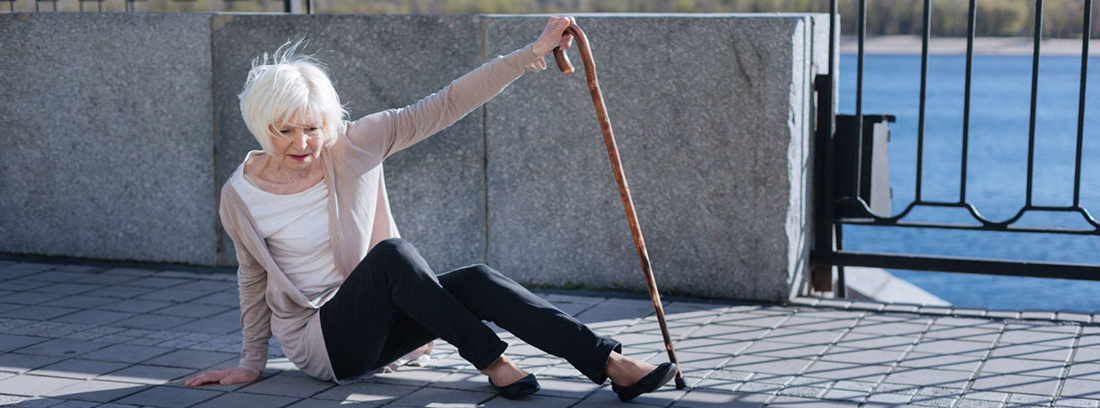 Síndrome post caída: caída de mujer mayor en la calle apoyándose en un bastón