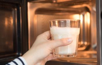 Cocinar con microondas: mano metiendo un vaso de leche en un microondas