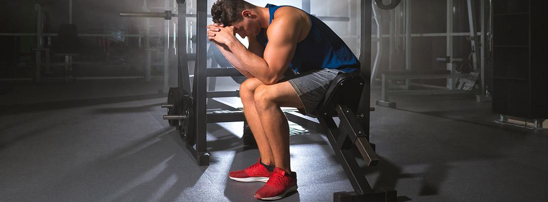Consecuencias de practicar ejercicio físico en exceso: hombnre deportista sentado en un gimnasio con las manos apoyadas en la cabeza