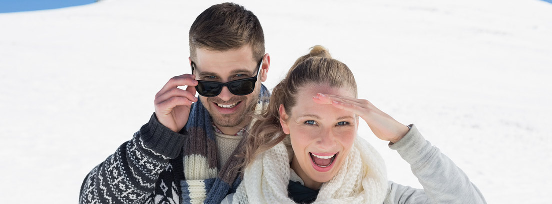 Fotoqueratitis: pareja de jóvenes en la nieve protegiéndose con gafas de sol
