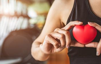 Síndrome del corazón de atleta: mujer deportista con un corazón de plástico en las manos