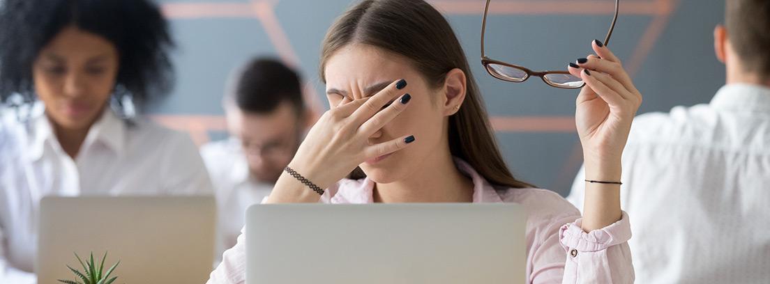 Visión borrosa repentina: mujer con los dedos en los ojos con problemas de visión