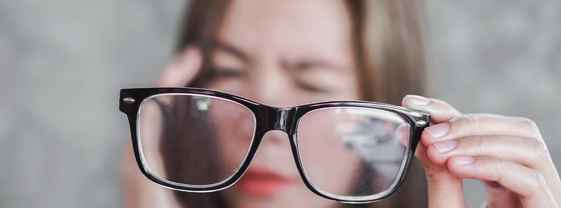 Visión borrosa repentina: Mujer sosteniendo anteojos con dolor de cabeza por visión borrosa de ojos