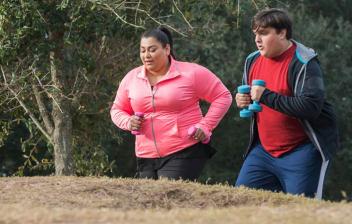 Estudio científico que confirma la necesidad del ejercicio para perder grasa: Un hombre y una mujer con exceso de peso realizando ejercicio por el campo