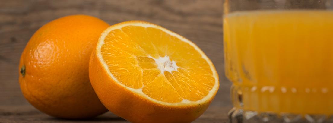 La naranja, mucho más que vitamina C: naranja partida por la mitad y un vaso de zumo al lado