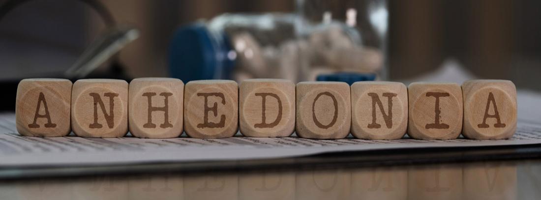 ¿Qué es la anhedonia o falta de placer?: palabra anhedonia en cubos de madera