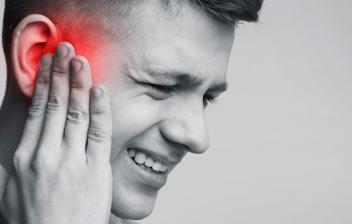 Causas y tratamiento para el dolor de oídos:chico joven con la mano en el oído, con síntomas de dolor
