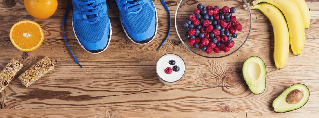 Alimentación para recuperarse tras una maratón: zapatillas de deporte, bol de frutas sobre tabla de madera