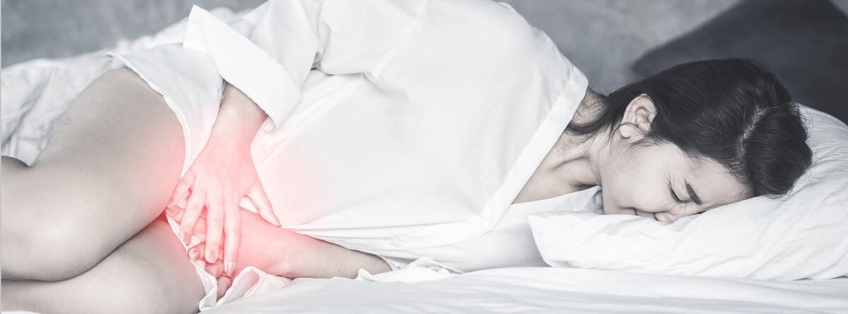 Glándula de Bartholino y Bartholinitis: mujer tumbvada con dolor en sus genitales