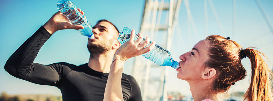 Bebidas deportivas: chico y chica bebiendo agua después de hacer ejercicioi