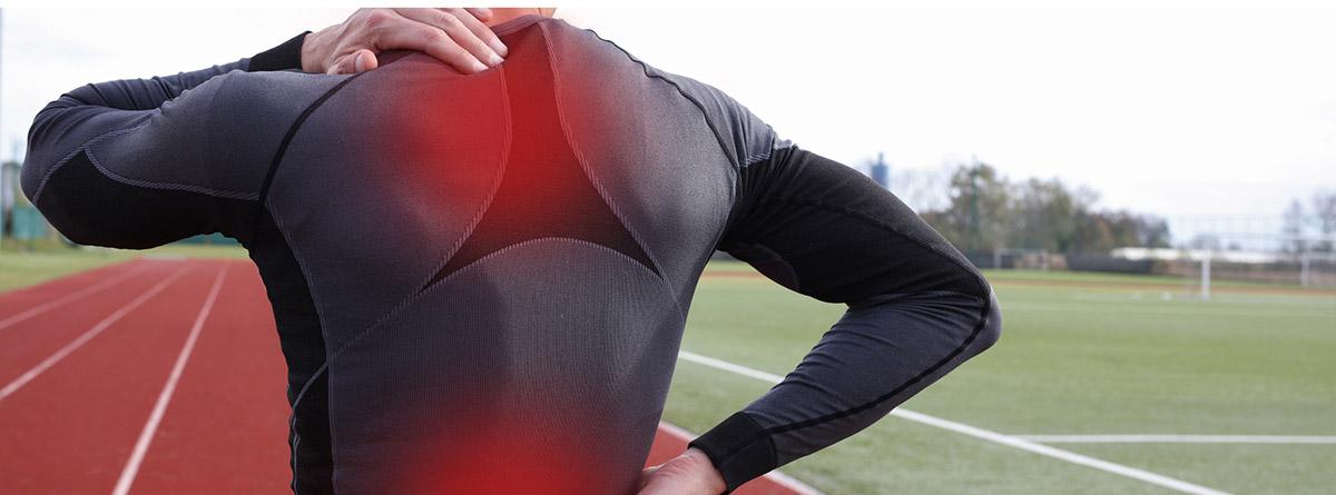 ¿Cómo prevenir el dolor de espalda al corredor?: deportista en pista de atletismo con problemas en la espalda
