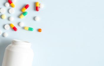 ¿Qué son y qué ventajas tienen los medicamentos combinados?: 3 frascos abiertos de medicamentos y pastillas alrededor