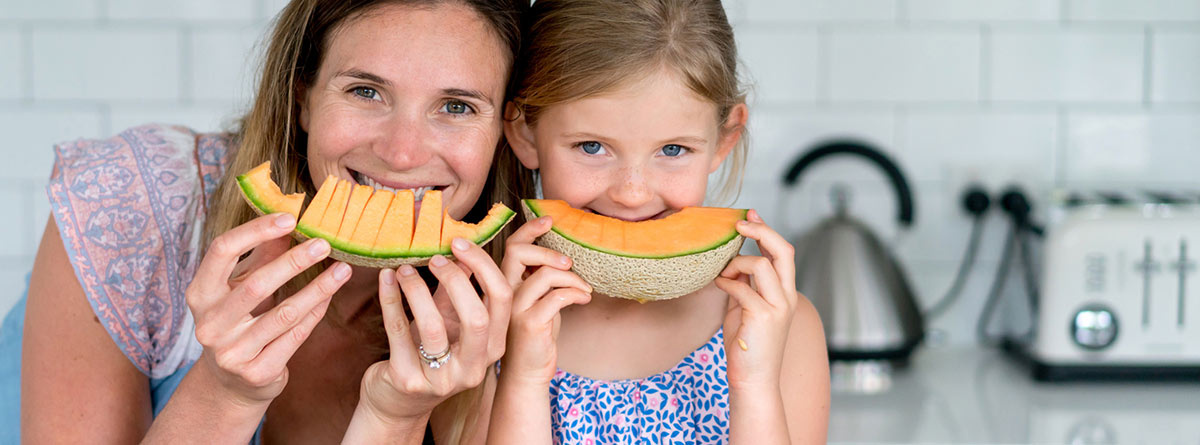 Meón: madre e hija comiendo una raja de melón