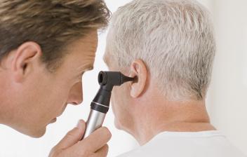 ¡Qué hace un otorrino y cuándo visitarlo?: otorrino inspecionando el oído de un paciente en la consulta