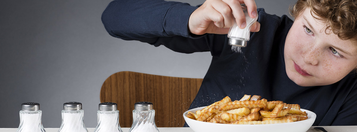 ¿Cómo reducir el consumo de sal en los niños?: niño echando sal en las patatas fritas y varios saleros encima de la mesa