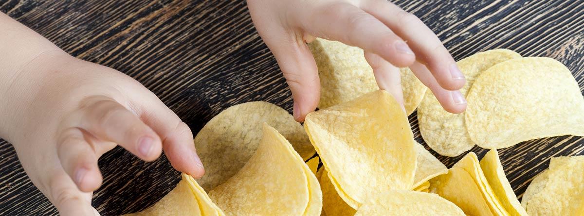 Cuanta sal pueden tomar los niños: manos de niño cogiendo patatas fritas