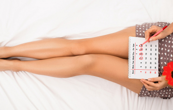 Sangrado de implantación: mujer tunbada con un calendario de días de embarazo y una flor roja al lado