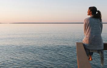 Chica sentada sobre una barandilla mirando al horizonte