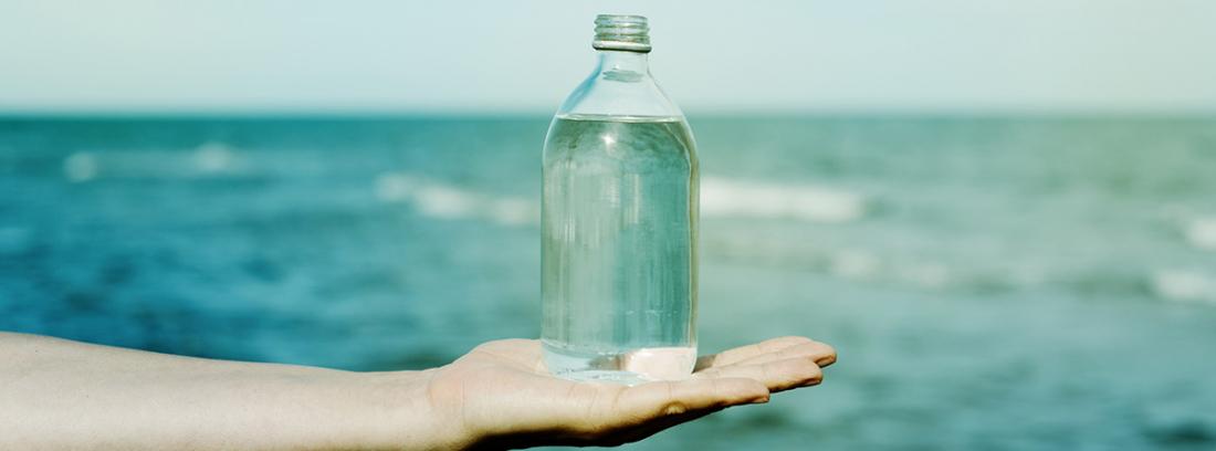 Propiedades del agua de mar: botella de agrua sobre mano extendida y el mar al fondo