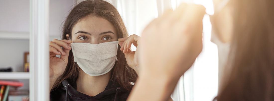 Síndrome de la cara vacía: chica joven con mascarilla ante un espejo