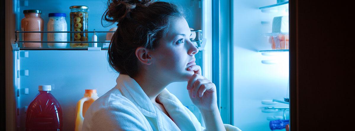 Hambre emocional: chica joven de noche con la puerta del frigorífico abierta mirando los alimentos