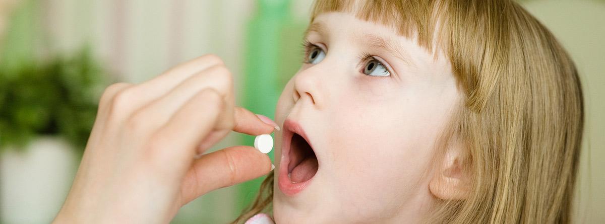 Uso correcto de medicamentos en niños: madre dando una pastilla a una niña