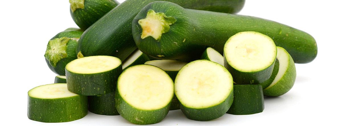 Beneficios del calabacín: Calabacines enteros y rodajas de calabacín
