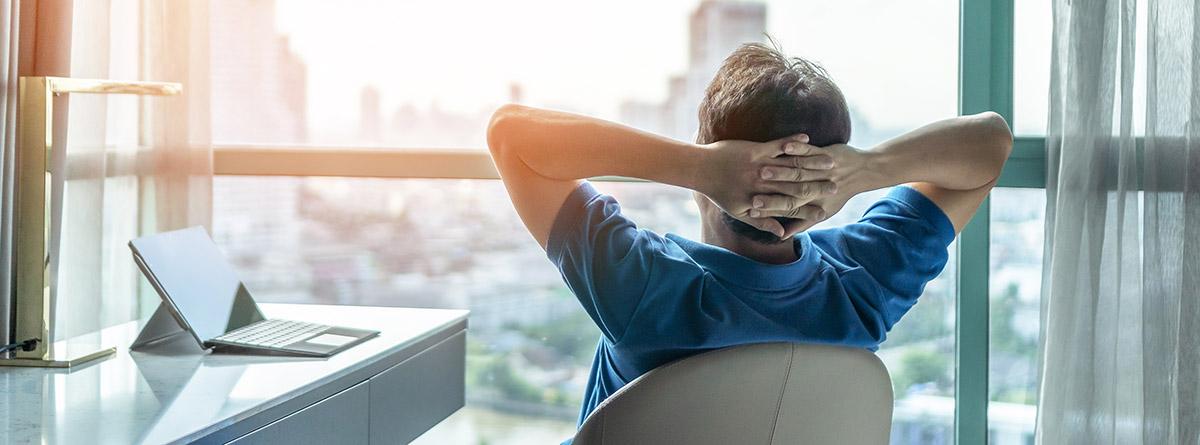 Técnica Niksen: hombre sentado con las manos en la nuca mirando hacía la ventana