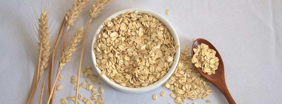 Beneficion del germen de trigo: bol con germen de trigo triturado una cuchara de madera y espigas de trigo