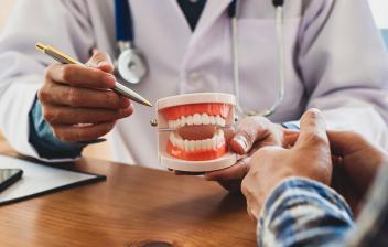 ¿Por qué se retraen las encías?: médico explicando a paciente las enfermedades de las encias con una dentadura artificial en la mano